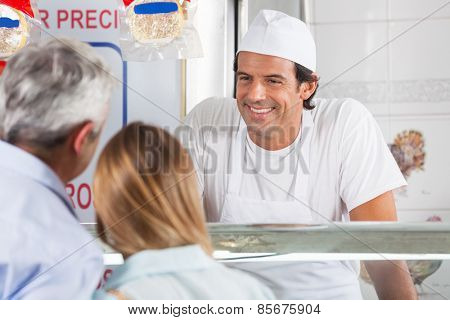 Friendly male butcher smiling at customers in shop