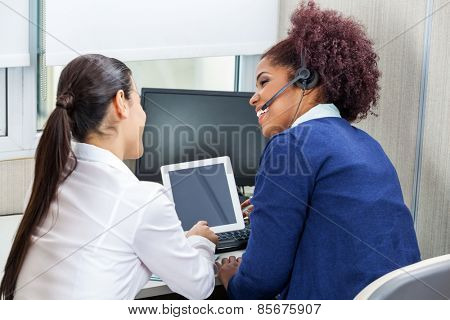 Rear view of happy female call center employees discussing while using digital tablet in office
