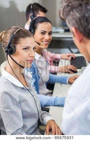 Female customer service executives looking at manager while sitting at desk in call center