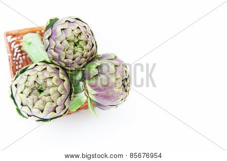 Bunch Of Three Artichokes In Basket White Background