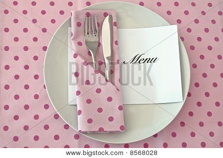 Table place setting with menu and spotted tablecloth