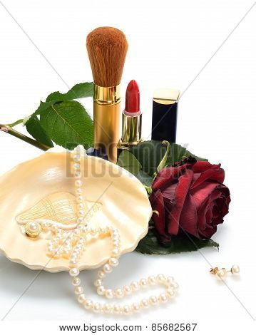 Women's jewelry, cosmetics and a rose in still life