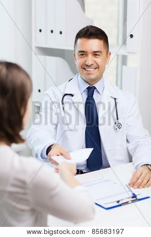 medicine, health care, meeting and people concept - smiling doctor with clipboard and laptop computer giving medical prescription or certificate to young woman at hospital