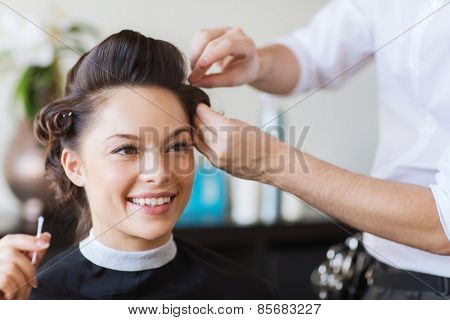 beauty, hairstyle and people concept - happy young woman with hairdresser making hairdo at salon