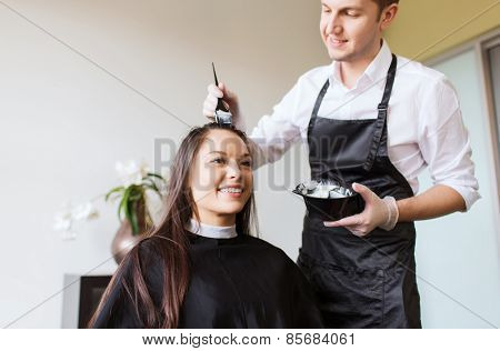 beauty and people concept - happy young woman with hairdresser coloring hair at salon