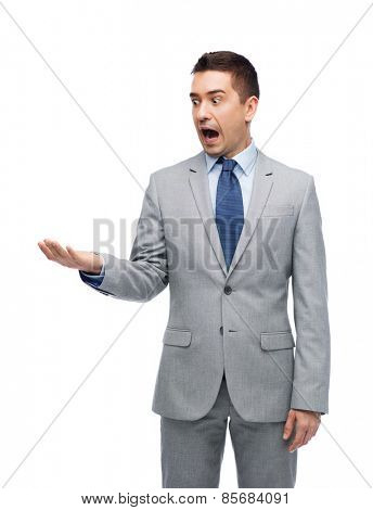 business, people, emotions and failure concept - shocked businessman in suit looking to his empty hand