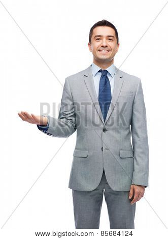 business, people and office concept - happy smiling businessman in suit showing something imaginary on empty palm