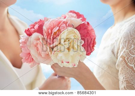 people, homosexuality, same-sex marriage and love concept - close up of happy married lesbian couple with flower bunch blue sky background
