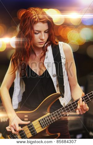 music, people, musical instruments and entertainment concept - red haired woman playing guitar on stage