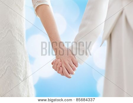 people, homosexuality, same-sex marriage and love concept - close up of happy married lesbian couple hugging over blue lights background