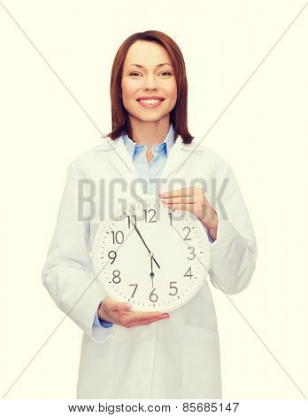 healthcare and medicine concept - smiling female doctor with wall clock