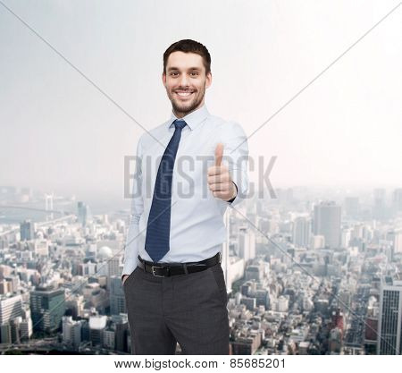 business and office concept - handsome businessman showing thumbs up