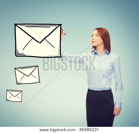 office, business and new technology concept - smiling businesswoman drawing envelope on virtual screen