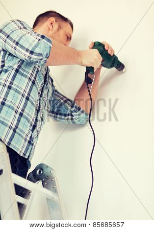 repair, building and home concept - close up of male with electric drill making hole in wall