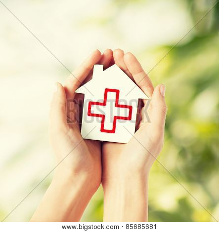 healthcare, medicine and charity concept - hands holding white paper house
