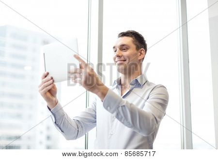 business, technology, internet and office concept - smiling businessman with tablet pc computer in office