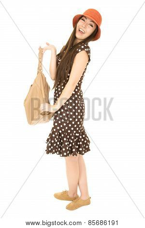 Smiling Asian American Teen Girl Holding A Brown Purse Wearing Polka Dot Dress