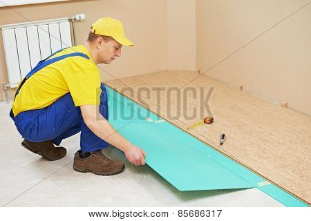 One carpenter worker laying cork boards during indoors flooring work