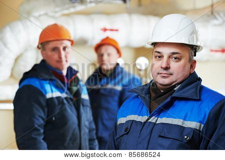 three repairman engineer of fire engineering system or heating system open the valve equipment in a boiler house