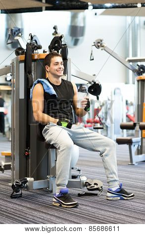 sport, fitness, equipment, lifestyle and people concept - smiling man exercising on gym machine
