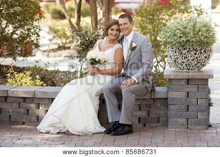 Young newly married couple in garden looking at camera