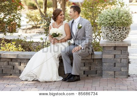 Newly married couple looking at each other in garden
