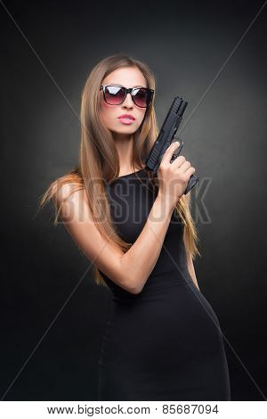 girl in a black dress and Sunglasses holding a gun