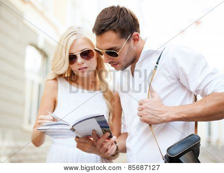 summer holidays, dating and tourism concept - couple with tourist book in the city