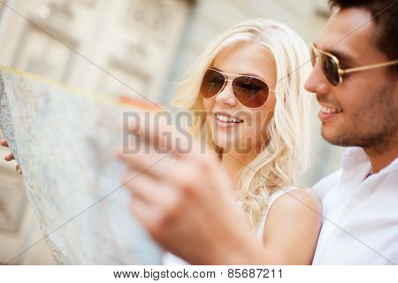 summer holidays, dating and tourism concept - couple with map in the city