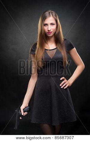 girl in a black dress holding a gun