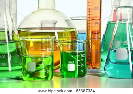 Close up view of various laboratory glassware on reflective table