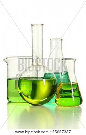 Assortment of laboratory glassware with green liquid isolated over white background -With clipping path on glass