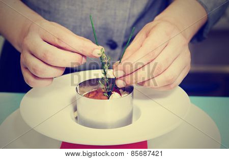 Chef is serving risotto with stainless steel form, toned image
