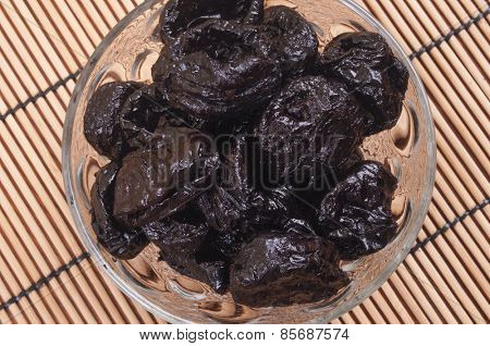 Prunes in a glass bowl - aerial view