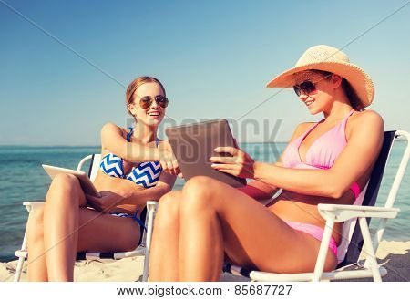 summer vacation, travel, technology and people concept - smiling women with tablet pc computers sunbathing in lounge on beach