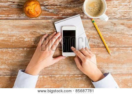 business, education, people and technology concept - close up of female hands touching smartphone blank screen with  notebook, muffin and coffee cup on table