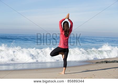 Young healthy Asian woman practicing yoga, meditating, and relaxing at beach