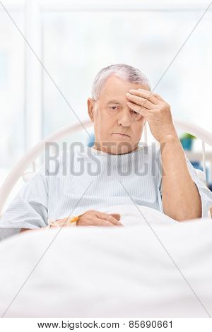 Mature patient having a headache and lying in a hospital bed