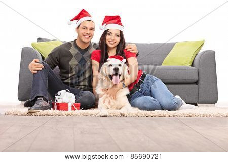 Studio shot of a young couple and their dog wearing Santa hats and celebrating Christmas seated on the floor next to a modern sofa isolated on white background