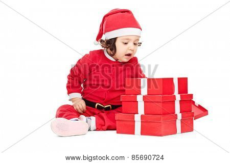 Curious baby girl sitting on the floor next to a pile of Christmas presents and peeking into one of the boxes isolated on white background