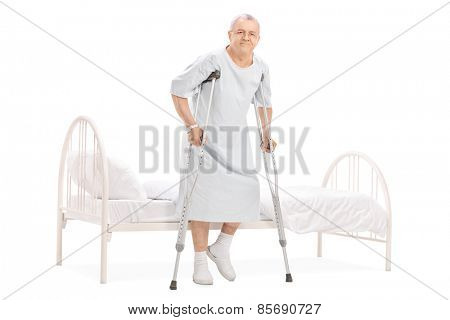 Full length portrait of a mature patient with crutches getting out of bed isolated on white background