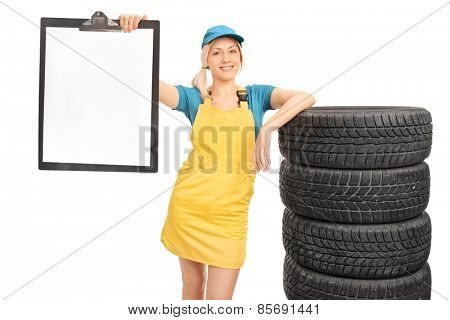 Studio shot of a beautiful blond female mechanic leaning on a stack of tires and holding a clipboard with a blank paper on it isolated on white background