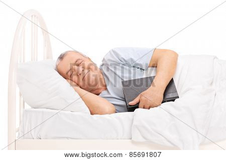 Senior sleeping in a bed covered with a blanket and holding a book isolated on white background