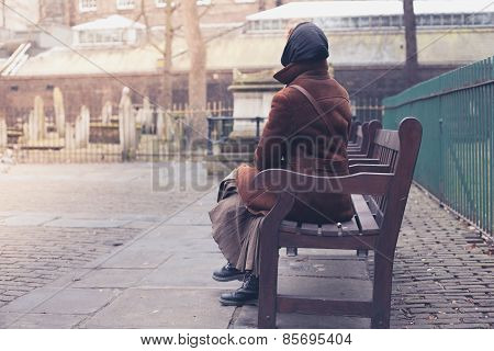 Woman Sitting On Bench In Graveyard