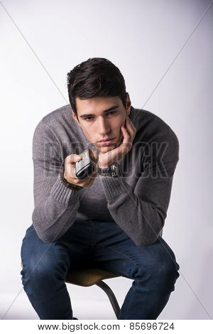 Handsome Young Man Holding Remote Control Bored Or Tired