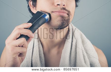 Young Man Shaving Half Of His Beard