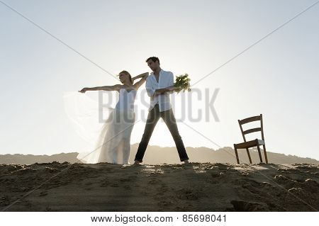 Silhouette of couple kissing and flirting on sand dune