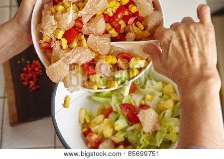 Mixing fresh fruit and vegetables for salad