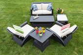image of manicured lawn  - Comfortable deep modern garden furniture with stylish armchairs and a two seater settee arranged on a neat manicured green lawn with tables decorated with potted plants high angle view - JPG