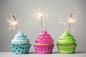 picture of cupcakes  - Row of three cupcakes with sparklers - JPG